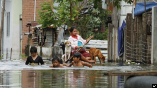 Residents travel on a flooded street in Phnom Penh September 26, 2011.The death toll from flooding in Thailand since mid-July has risen to 158, while 61 people have died in neighbouring Cambodia in the past two weeks, authorities in the two countries said