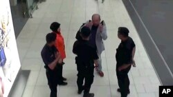 In this image made from airport closed circuit television video and provided by Fuji Television, Kim Jong Nam, exiled half-brother of North Korea's leader Kim Jong Un, gestures towards his face while talking to airport security and officials at Kuala Lump