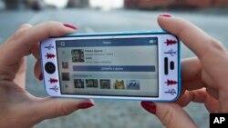 Un Russe surfent sur les réseaux sociaux avec son téléphone à Moscou, Russie, le 23 avril 2014.