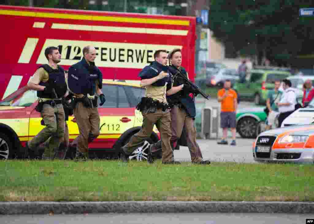 Police walk near a shopping center in Munich were a guman shot several people July 22, 2016.