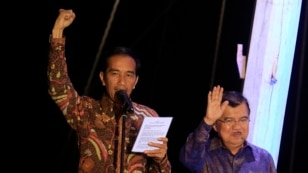 "Indonesian presidential candidate Joko ""Jokowi"" Widodo (L) gestures as delivers a speech, beside his running mate Jusuf Kalla, on a phinisi boat, a traditional Indonesian ship, at Sunda Kelapa port after he was declared the winner of the presidential elec"