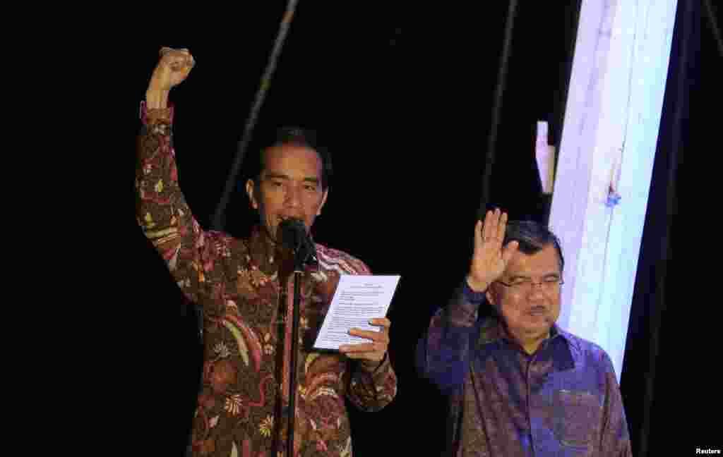"Presiden Indonesia terpilih Joko ""Jokowi"" Widodo mengangkat tangan saat menyampaikan pidato kemenangan, didampingi Wakil Presiden terpilih Jusuf Kalla, di atas kapal phinisi di Pelabuhan Sunda Kelapa (22/7). (Reuters/Beawiharta)"