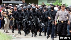 Members of the anti-terror police arrive at the village of Batu Rengat, where police exchanged fire with suspects in a house in Bandung, West Java province, May 8, 2013.