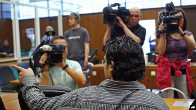 Al-Qaida suspect Rami Makanesi greets friends prior to the start of his trial in a court room in Frankfurt, May 9, 2011
