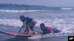 Shaun McLaughlin, 6, who was born without a right foot, gives surfing a try under the watchful eye of AmpSurf volunteers and instructors.