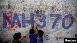 FILE - Children write messages of hope for passengers of missing Malaysia Airlines Flight MH370 at Kuala Lumpur International Airport, June 14, 2014.