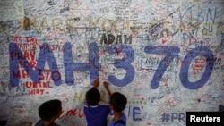 Anak-anak menulis pesan harapan bagi penumpang pesawat Malaysia Airlines bernomor penerbangan MH370 di bandara internasional Kuala Lumpur. (Reuters/Samsul Said)