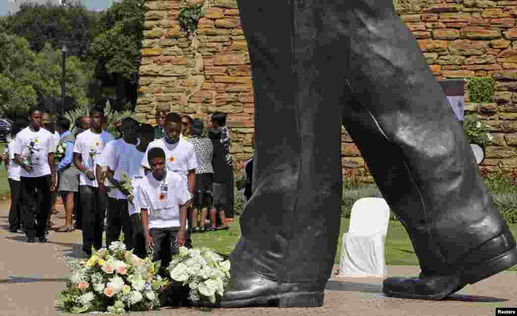 School students lay wreaths during the official ceremony marking the first anniversary of the death of former South African President Nelson Mandela, at the world's largest Mandela statue at the Union Buildings in Pretoria, South Africa.
