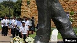 Para siswa meletakkan karangan bunga di bawah patung Nelson Mandela di Johannesburg memperingati setahun wafatnya mendiang pemimpin anti apartheid itu.