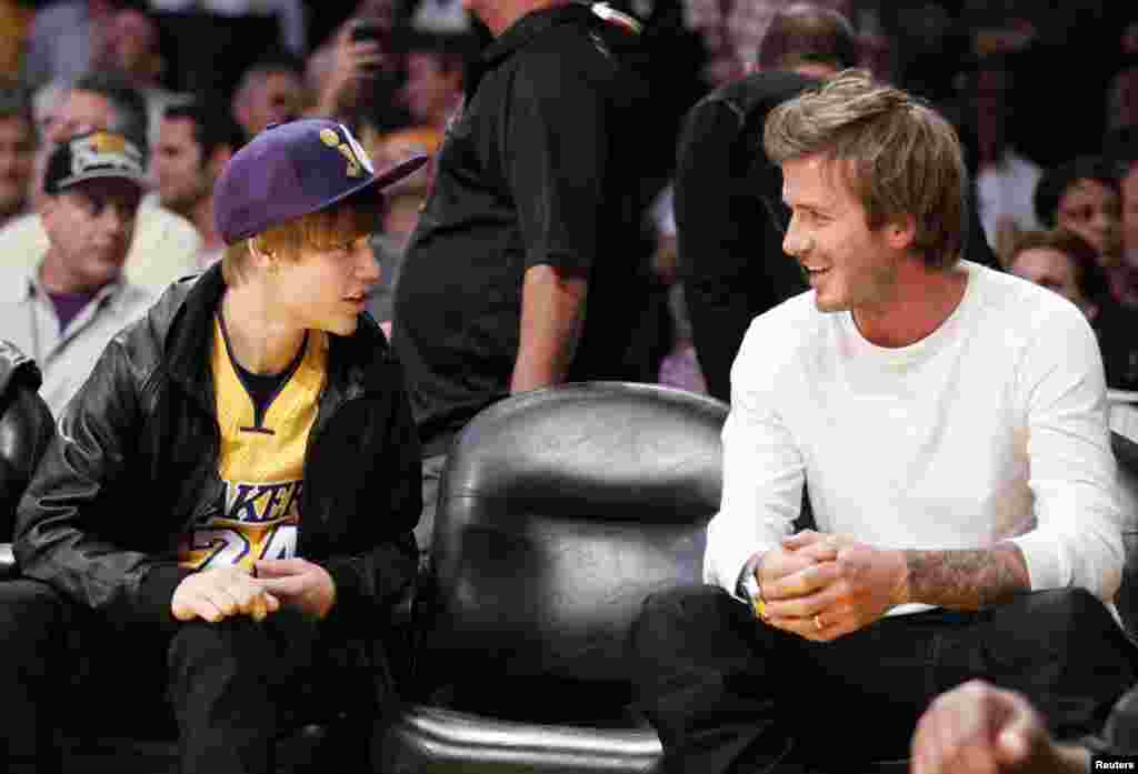 Justin Bieber chats with David Beckham during the NBA game between the Los Angeles Lakers and the Houston Rockets in Los Angeles, California, October 26, 2010.