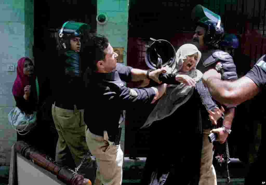A police officer scuffles with a protester during clashes in Lahore, Pakistan, June 17, 2014.