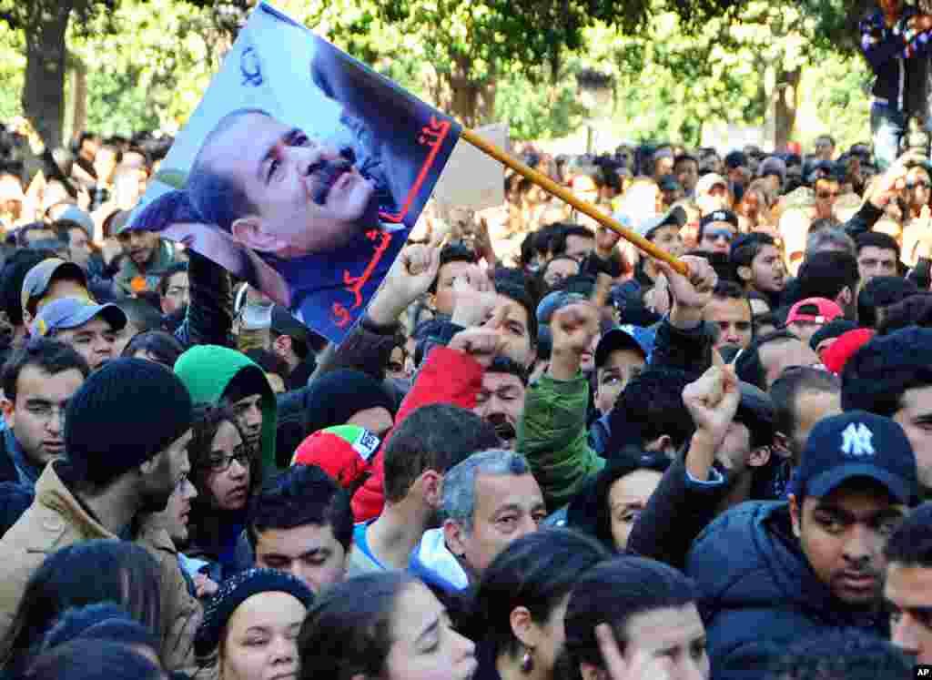 当突尼斯一个抨击伊斯兰主义者领导的政府的反对派领导人2013年2月6日离开家被枪杀之后,抗议者聚集在突尼斯主要的大街上。
