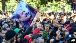 Protesters gather on Tunis' main avenue after a Tunisian opposition leader critical of the Islamist-led government was gunned down as he left home, February 6, 2013.