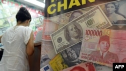 FILE - The U.S. dollar, Indonesian rupiah and Chinese renminbi currencies are displayed in the poster of a money exchange shop in Jakarta, June 12, 2013.