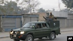 A Pakistani army vehicle patrols a street following a blast at a paramilitary camp in Bannu, Pakistan, December 24, 2011.