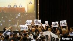 Para anggota parlemen pro-demokrasi mengangkat spanduk dan tulisan sebagai protes saat pejabat Beijing berpidato di parlemen Hong Kong (1/9).