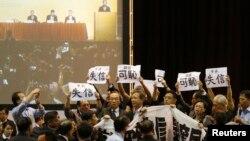 香港泛民議員在中國全國人大常委會副秘書長李飛講話時舉起標語抗議