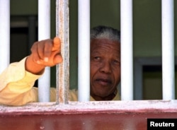 FILE: African National Congress (ANC) president Nelson Mandela stares out of the window of the prison cell he occupied on Robben Island for much of his 27 year incarceration.