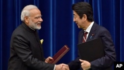 India's Prime Minister Narendra Modi, left, and Japan's Prime Minister Shinzo Abe shake hands after signing a joint statement at Abe's official residence in Tokyo, Japan.