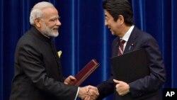 일본을 방문한 나렌드라 모디 인도 총리(왼쪽)가 11일 도쿄에서 아베 신조 일본 총리와 협정 서명식에 이어 악수하고 있다.