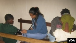 Mercer students Kamjeet Kaur (left) and Nancy Price check patients' vital signs at Chuluchosema clinic. (VOA/L.Masina)