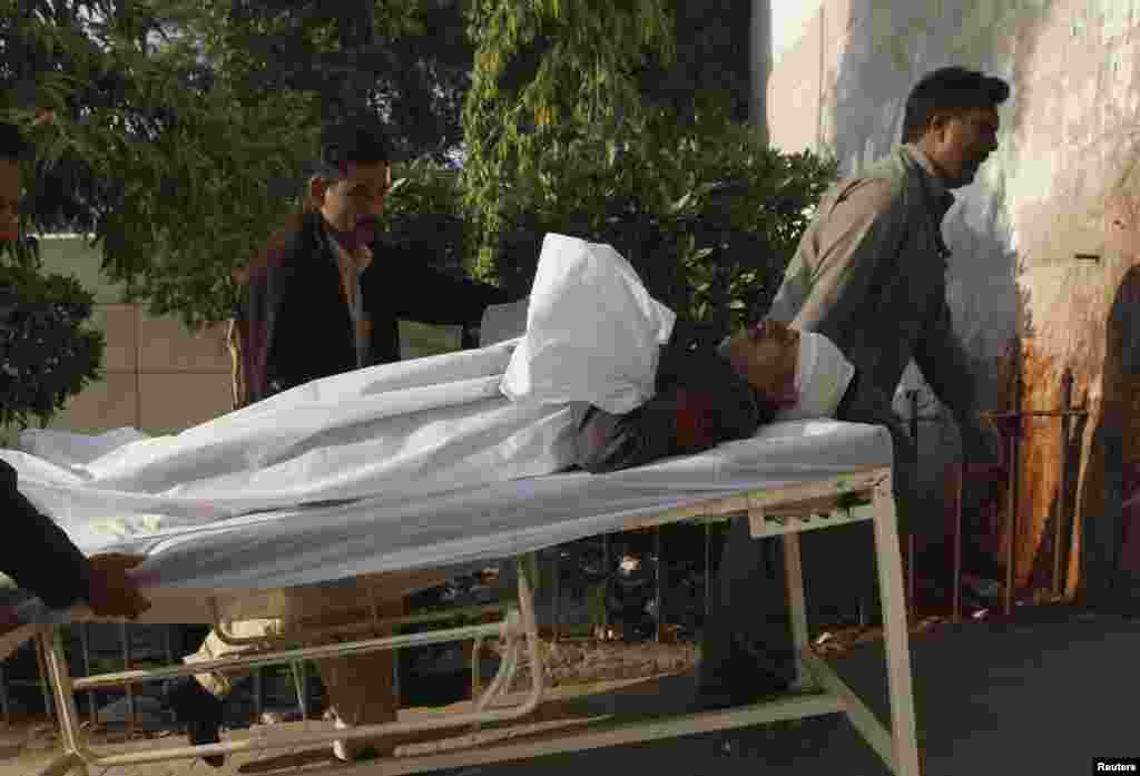 Men move a policeman by stretcher who was wounded after being hit by stones during a protest organized by Islami Jamiat-e-Talaba (JTI), the student wing of religious political party Jamaat-e-Islami (JI), against the satirical French weekly newspaper Charlie Hebdo, Jan. 16, 2015.