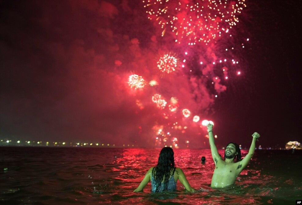 La gente observa los fuegos artificiales explotando sobre la playa de Copacabana durante las celebraciones de Nochevieja en Río de Janeiro, Brasil. (Foto AP)