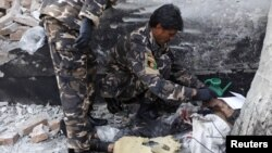 Petugas keamanan Afghanistan memeriksa lokasi ledakan bom bunuh diri di Kabul (21/11). Ledakan di dekat markas besar NATO ini menewaskan dua petugas keamanan Afghanistan dan melukai lima warga sipil.
