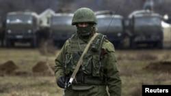 Seorang tentara yang dipercaya tentara Rusia, berdiri berjaga-jaga di luar pangkalan militer Ukraina di desa Perevalnoye dekat Simferopol.