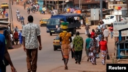FILE - People walk as security forces traveling in a truck patrol a street in the Ivory Coast in December 2010.