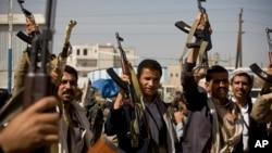 Pemberontak Syiah Houthi mengacungkan senjata mereka dalam bentrokan dekat istana Presiden di Sanaa, Yaman hari Senin (19/1).