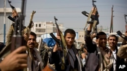 Houthi Shi'ite Yemeni show their weapons during clashes near the presidential palace in Sana'a, Yemen, Jan. 19, 2015.