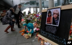 Portraits of two plane crash victims Natalia Soldatulina and Alexandra Pilip are placed near flowers and toys at an entrance of Pulkovo airport outside St. Petersburg, Russia, Nov. 4, 2015.