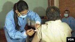 Una trabajadora de la salud aplica una vacuna contra COVID-19 a una persona en Tegucigalpa, Honduras. Foto de Oscar Ortuiz, VOA.