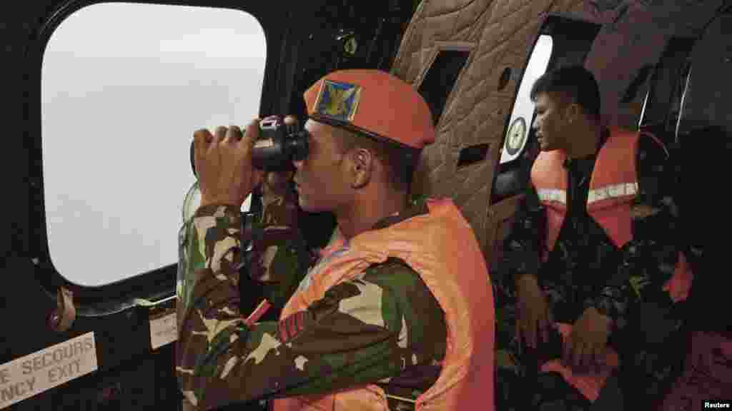 A crewmember of an Indonesian Air Force Super Puma helicopter of 6th Air Squadron uses a binocular to scan the horizon during a search operation for the victims of AirAsia Flight 8501 over the Java Sea, Jan. 1, 2015.