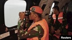 1일 에어아시아 사고 여객기 실종자들을 찾는 수색대가 헬리콥터 안에서 망원경으로 자바해를 내려다보고 있다.