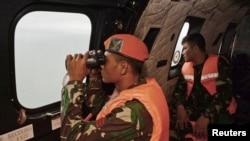 Prajurit TNI AU di helikopter Super Puma menggunakan teropong untuk memantau perairan setempat pada operasi pencarian korban jatuhnya pesawat AirAsia penerbangan 8501 di Laut Jawa, Kamis (1/1).