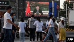 北京街头的行人观看电子屏幕上中国国家主席习近平通过视频在世卫大会视频开幕式上致辞。(2020年5月18日)