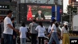 北京街头的行人观看电子屏幕上中国国家主席习近平。(2020年5月18日)