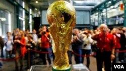Des visiteurs autour du trophée de Coupe du Monde de la FIFA à Zurich, en Suisse, 26 mars, 2006. (AP Photo / Keystone, Eddy Risch )