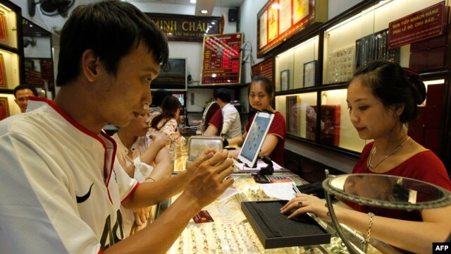 A man looks at a gold product at a Bao Tin Minh Chau gold shop in Hanoi on June 21, 2013.
