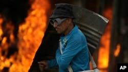 Un manifestante equipado con un escudo metálico camina frente a un autobús quemado el sábado en Caracas.
