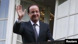 El presidente electo de Francia, Francois Hollande saluda desde el balcón de su cuartel de campaña, en Paris.
