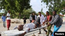 Residents transport a man wounded in crossfire during fighting between Somali government forces, backed by African Union troops, and Islamist militants in Madina District of Somalia's capital Mogadishu, Aug. 15, 2014.