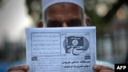 Seorang pria Pakistan memegang pamflet yang diduga disebarkan oleh militan Negara Islam (ISIS) di Peshawar, Pakistan, September 2014.
