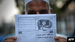 A Pakistani man holds a pamphlet, allegedly distributed by the Islamic State (IS), in the northwestern Pakistani city of Peshawar, Sept. 3, 2014 .