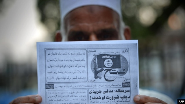 FILE - This photograph taken on Sept. 3, 2014, shows a Pakistani man holding a pamphlet, allegedly distributed by the Islamic State (IS), in the northwestern Pakistani city of Peshawar.