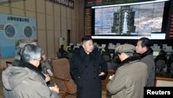 Pemimpin Korea Utara Kim Jong-Un (tengah) mengunjungi situs peluncuran satelit Laut Barat di Cholsan, provinsi North Pyongan. (Reuters/KCNA)