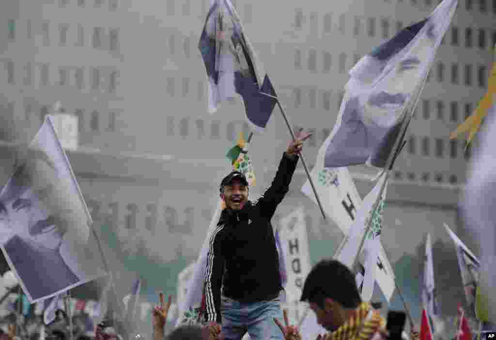A supporter of the pro-Kurdish Peoples' Democratic Party (HDP) flashes the V-sign as others wave flags of imprisoned Kurdish rebel leader Abdullah Ocalan, during a rally in Istanbul, Turkey, a day after the elections. President Recep Tayyip Erdogan's long-ruling Justice and Development Party (AKP) has suffered surprisingly strong losses in parliament that will force it to seek a coalition partner for the next government.