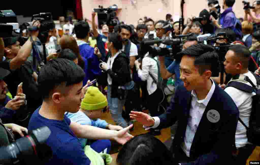 El candidato local Kelvin Lam celebra con sus seguidores después de que se anunció que ganó las elecciones del consejo local en su distrito, en una mesa electoral en el distrito South Horizons West en Hong Kong, China, el 25 de noviembre de 2019 (hora local).
